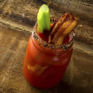 Two mason jar Bloody Mary or Caesar  with  bacon on wood background